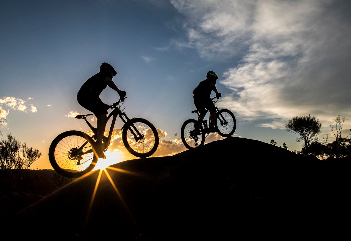 Kids riding mountain bikes in front of sunset