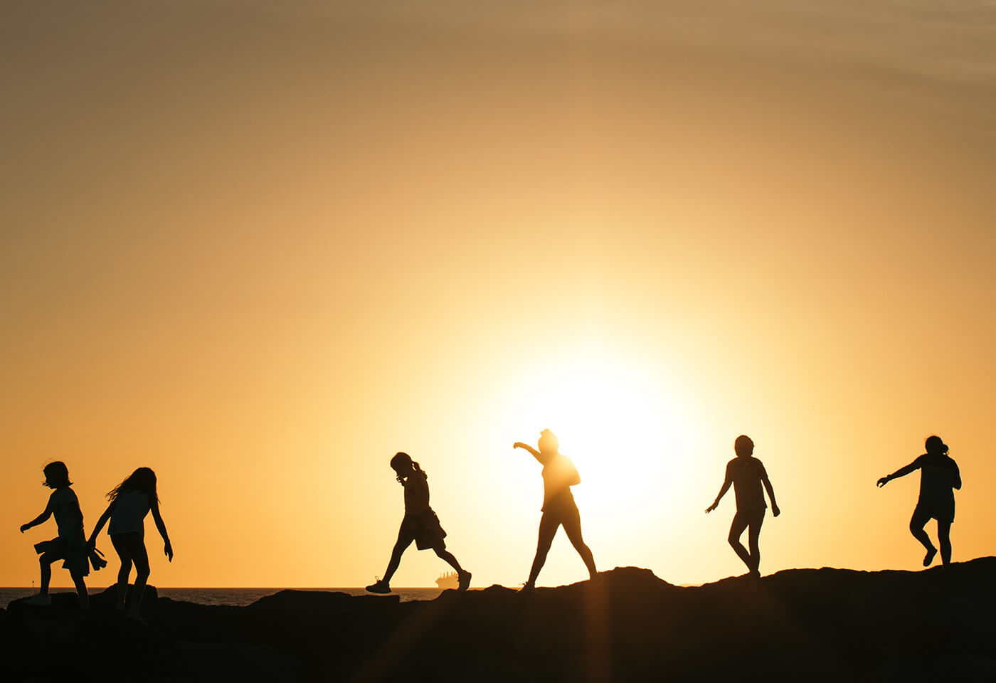 Silhouettes of children walking with sunrise in the background