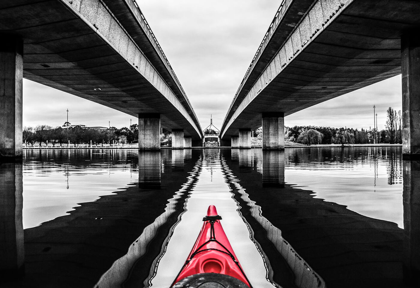 image of red kayak tip between two bridges