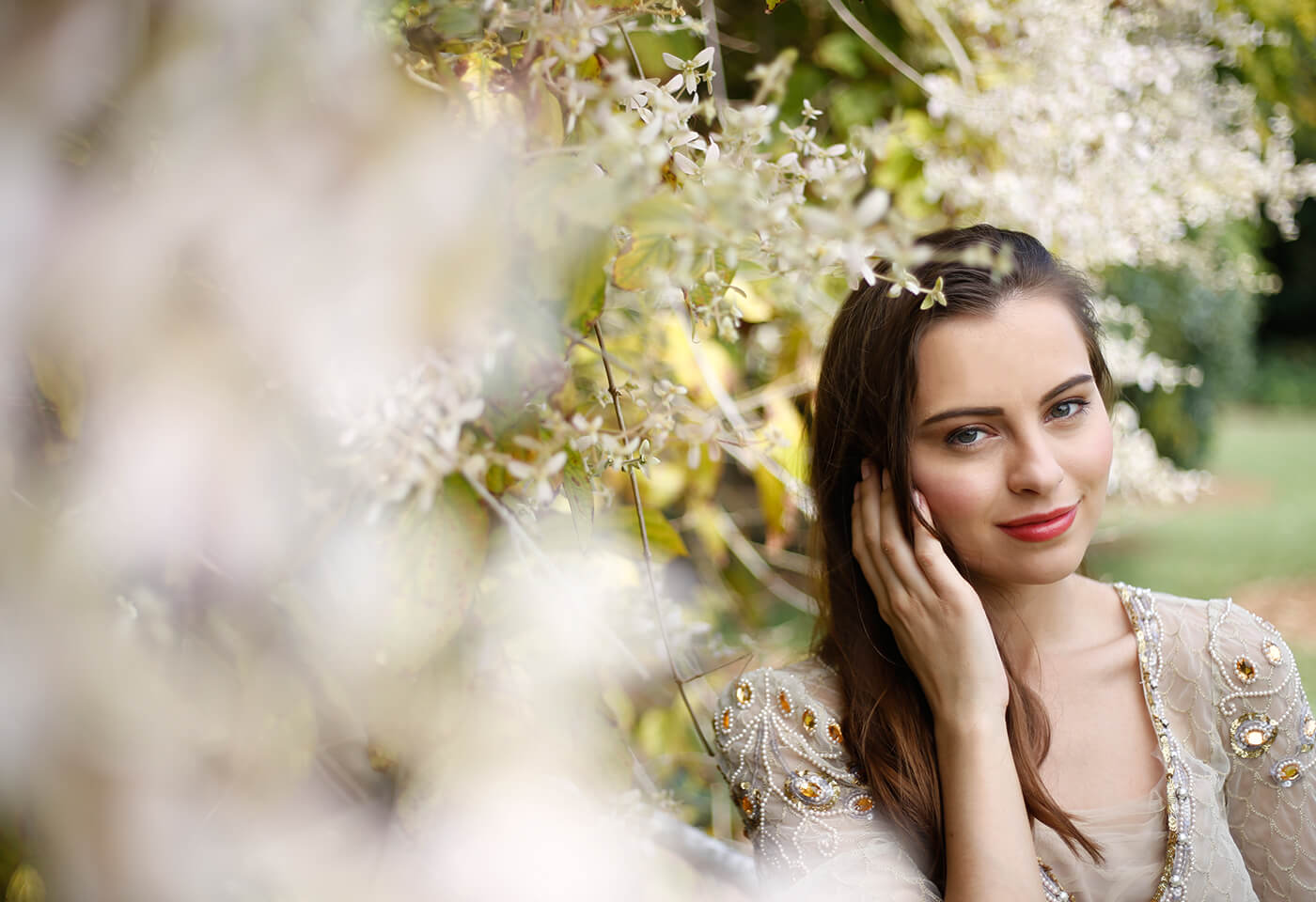 Young brunette lady among flowers taken using a Canon DSLR camera and prime lens
