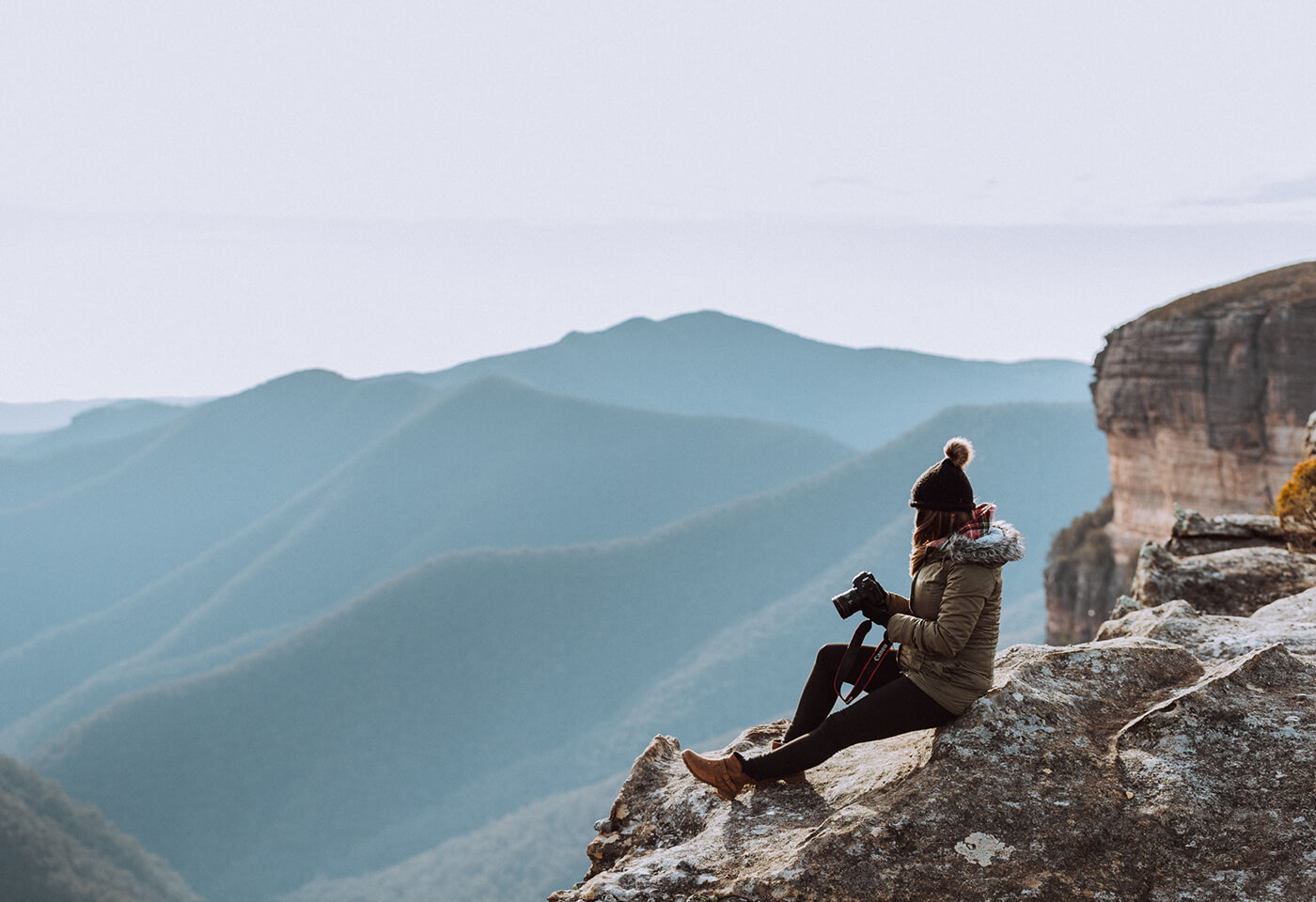 Photograoher with EOS 6D Mark II sitting on mountain top
