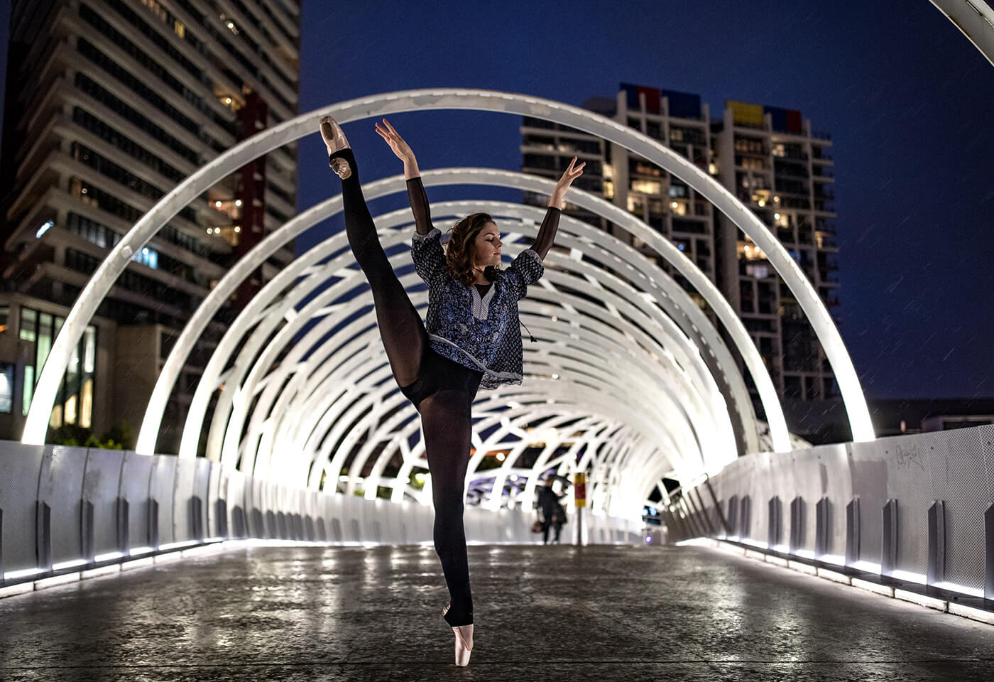 Ballet dancer photographed performing on bridge at night