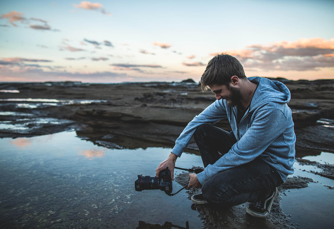 Photographer holding Canon 6D Mark II by rock pool