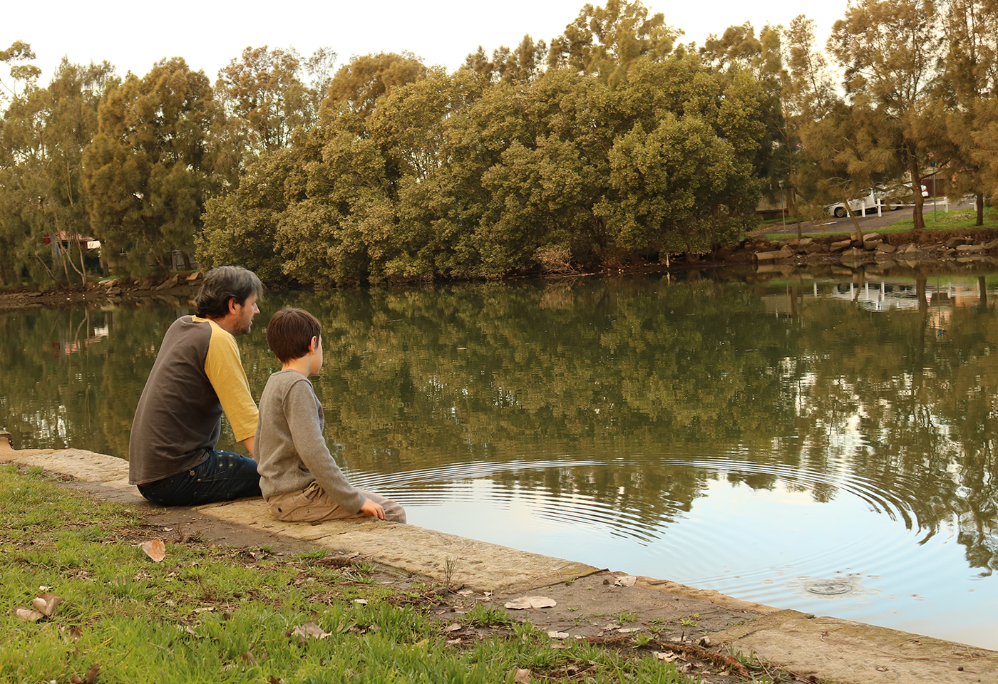 Father and son sitting by the lake