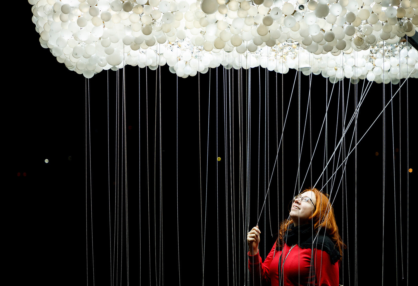 Woman pictured underneath a large group of lightbulbs on strings