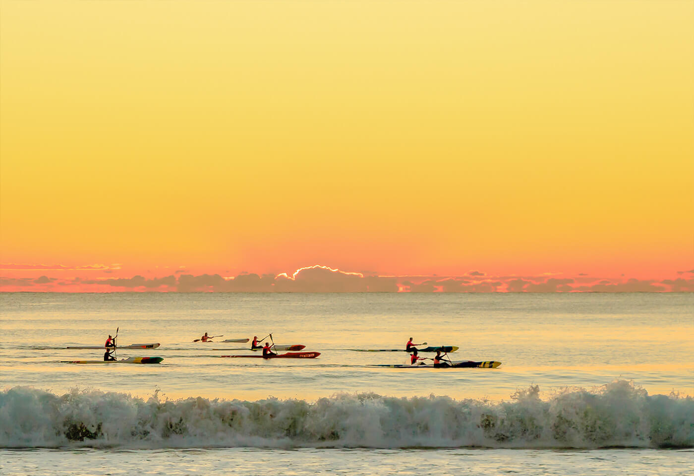 Surfers on water with sunset on the horizon