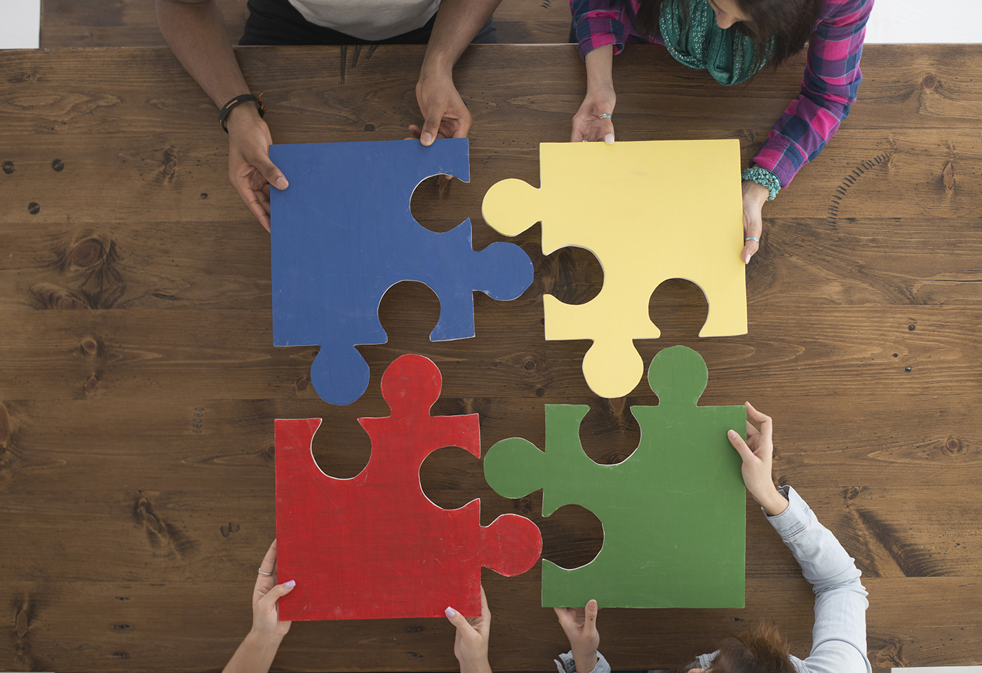 4 people connecting puzzle pieces