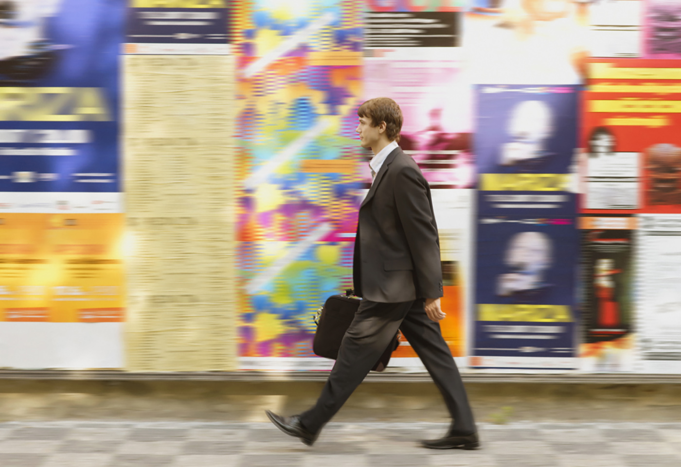 Man walking past colourful posters