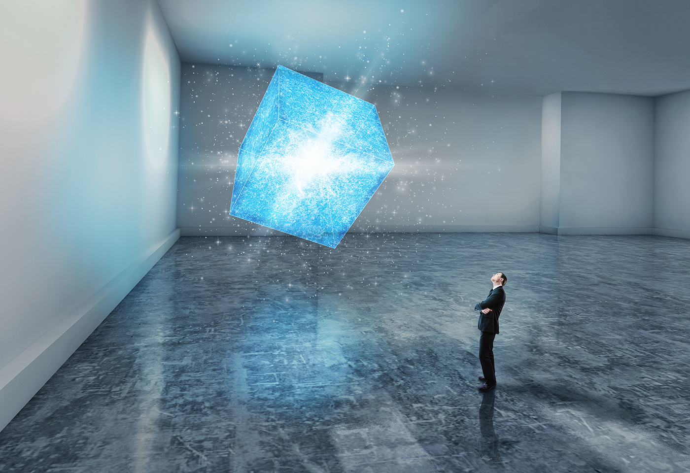 Man in suit looking at a light blue elevated cube