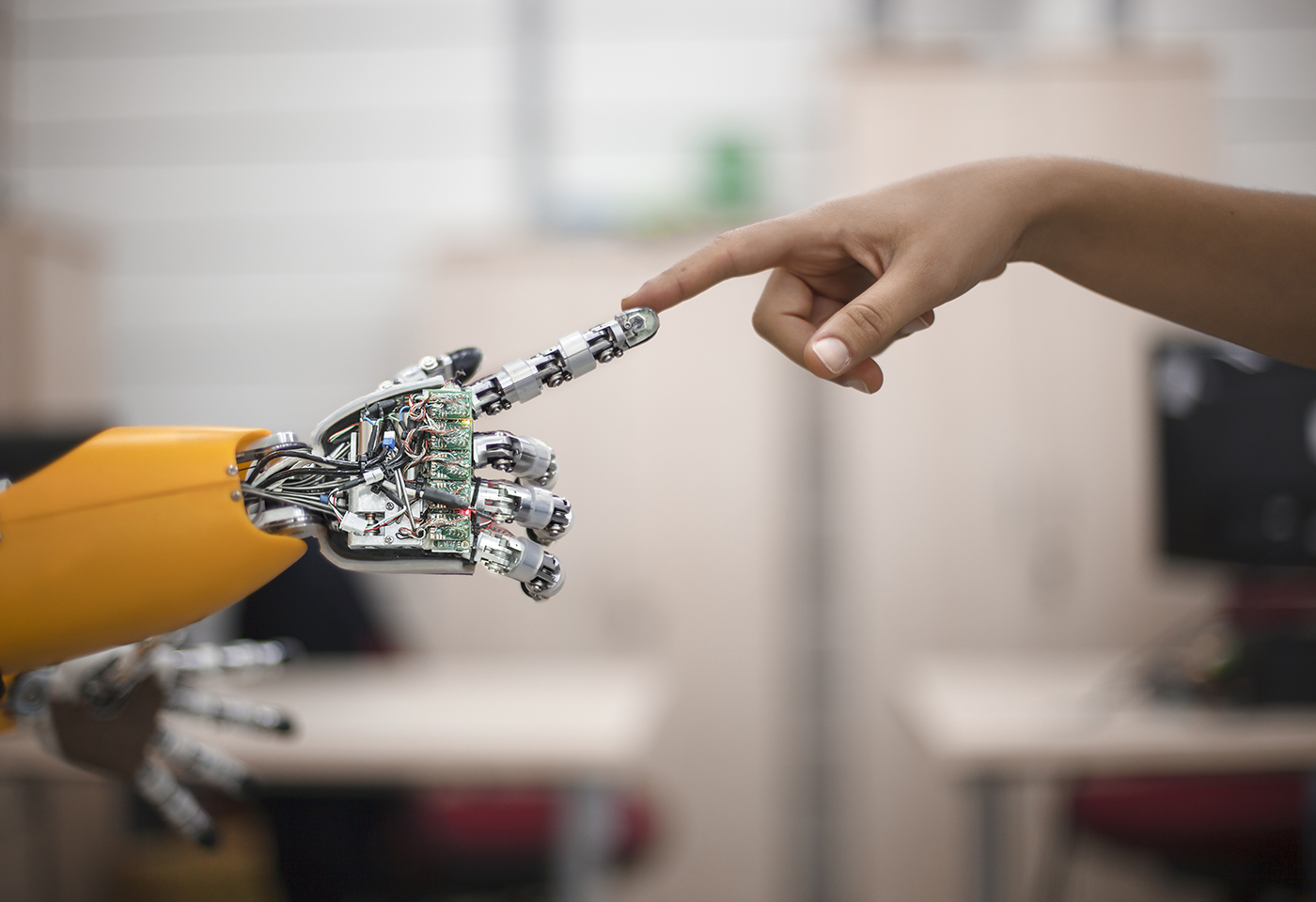 Robotic hand touching finger of human hand