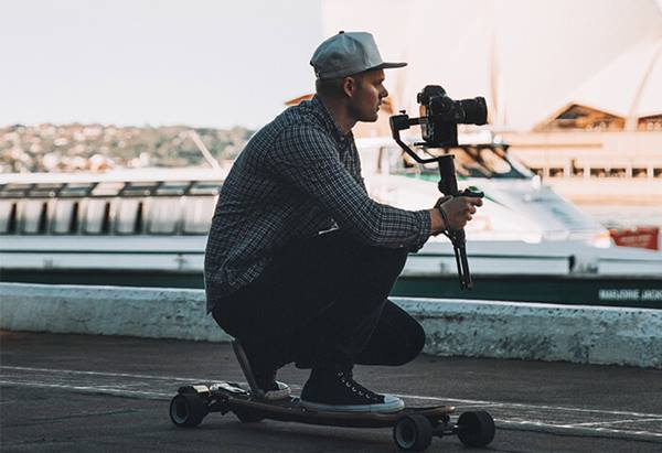 Photographer on skateboard with Canon EOS