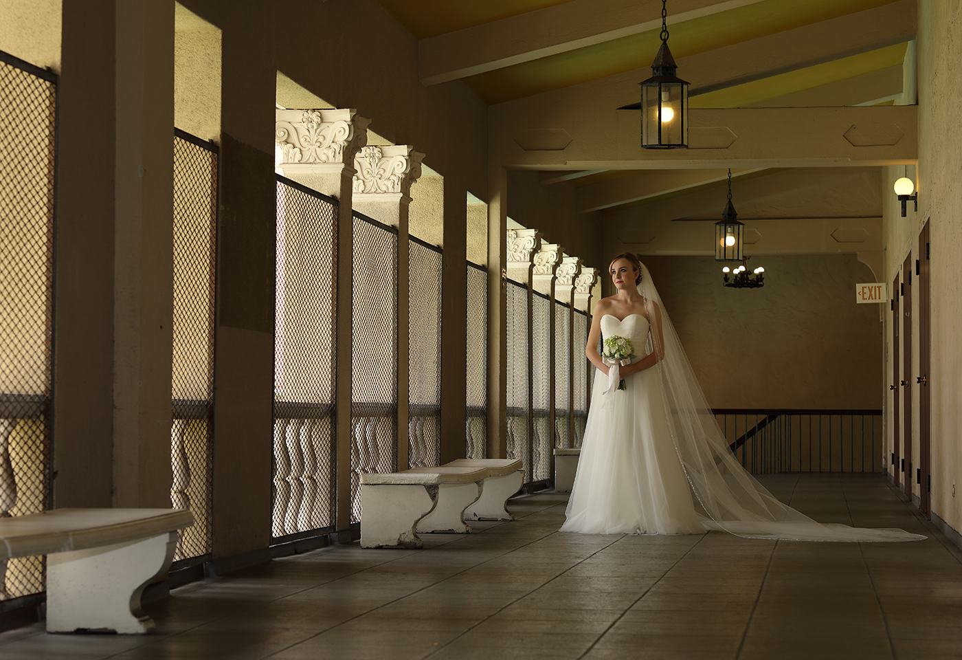 wide shot image of bride with bouquet standing in hallway