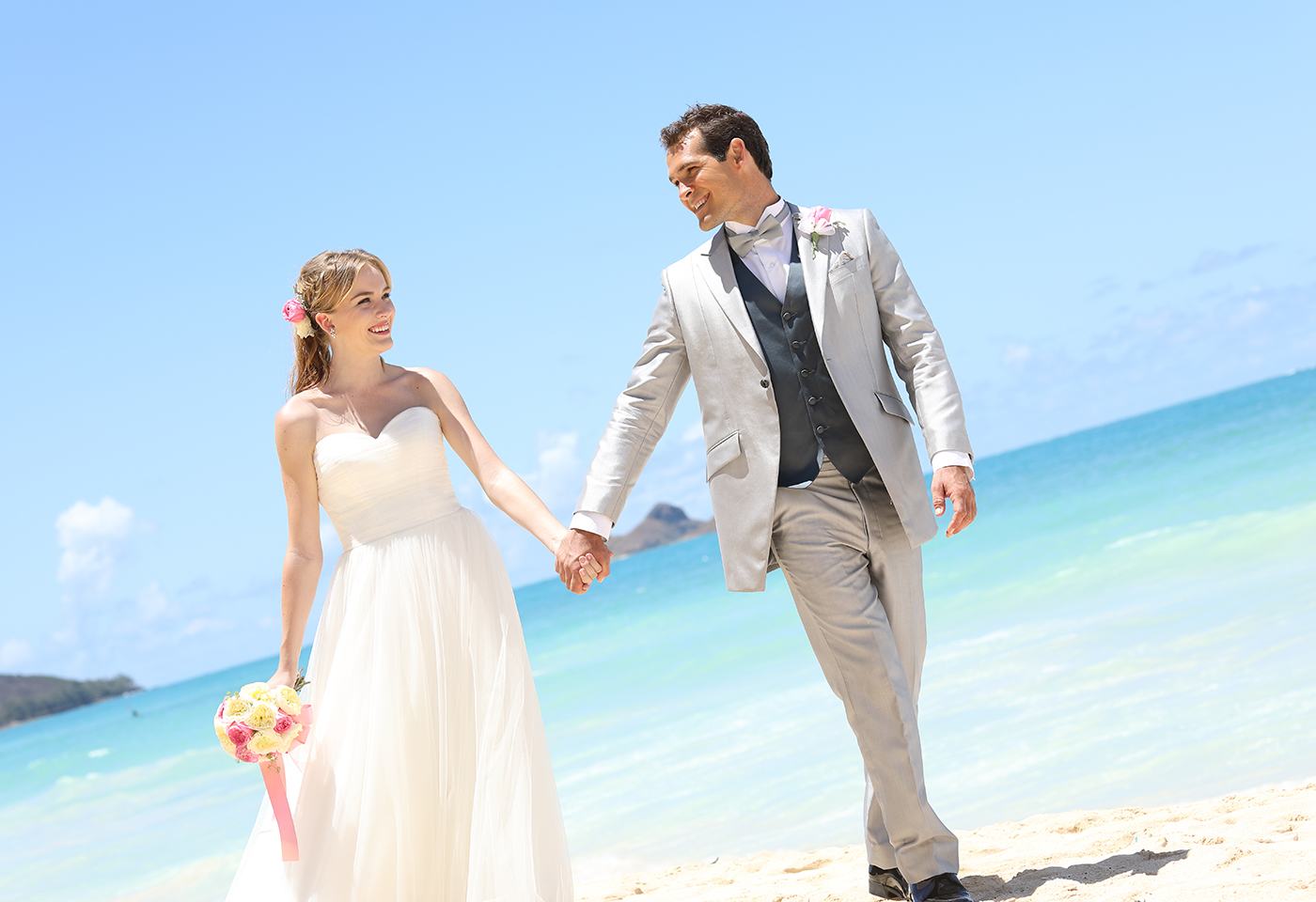 portrait  image of bride and groom holding hands on beach