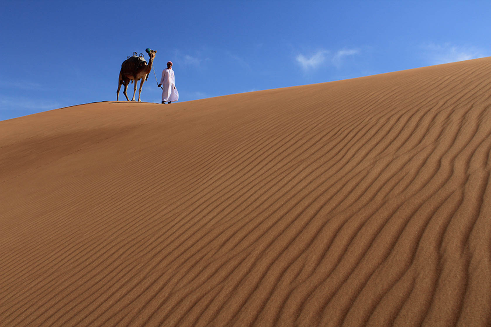 Man leading a camel across the sand dunes taken with Canon EOS 1300D DSLR camera