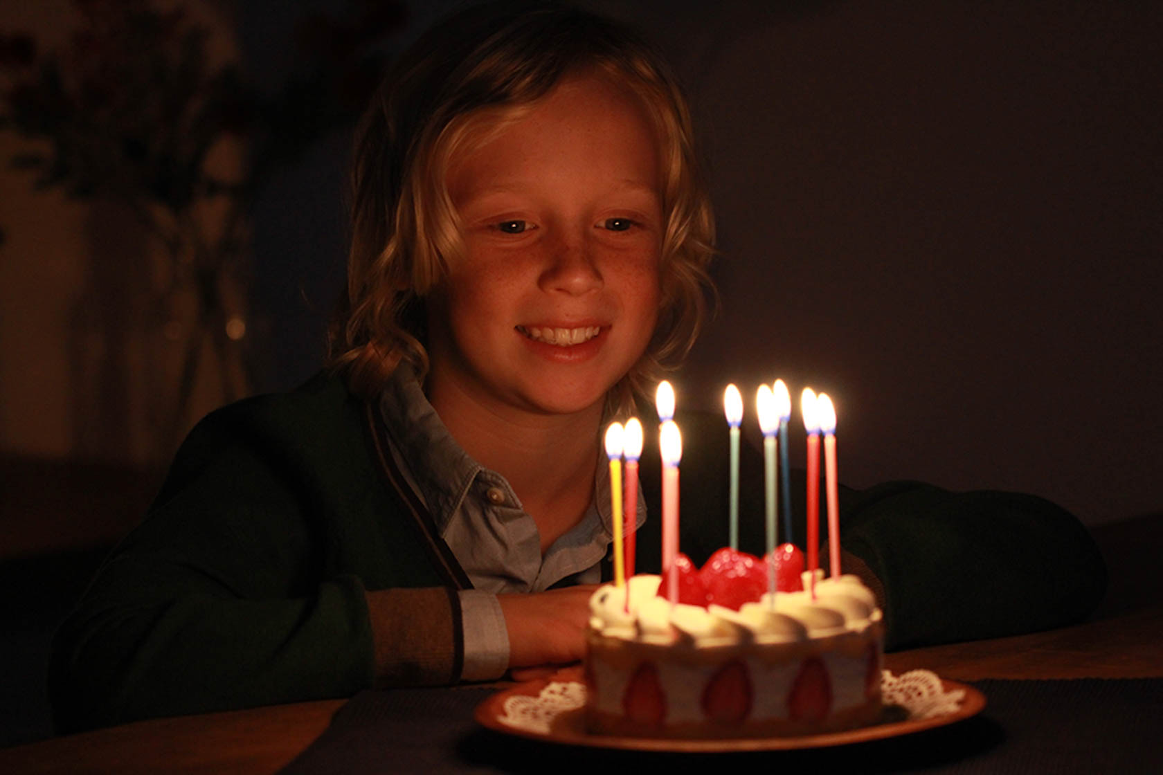 Young child sitting in front of a birthday cake with candles taken with Canon EOS 1300D DSLR camera