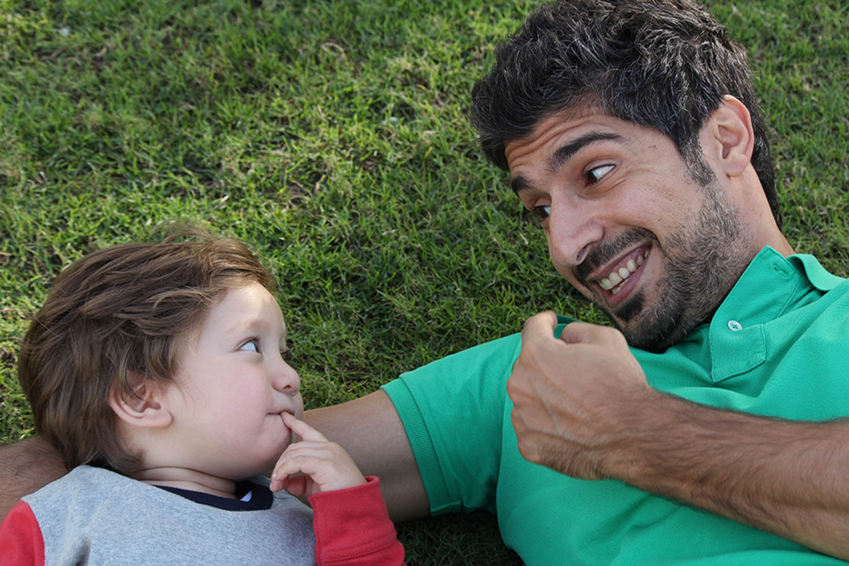 Father and son lying on grass taken with Canon EOS 1300D DSLR camera