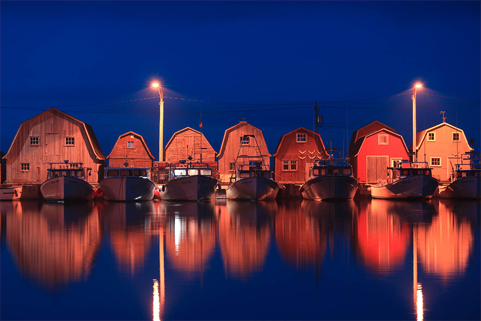 Photo of boat sheds lit at night shot on Canon EOS M10 Compact System Camera