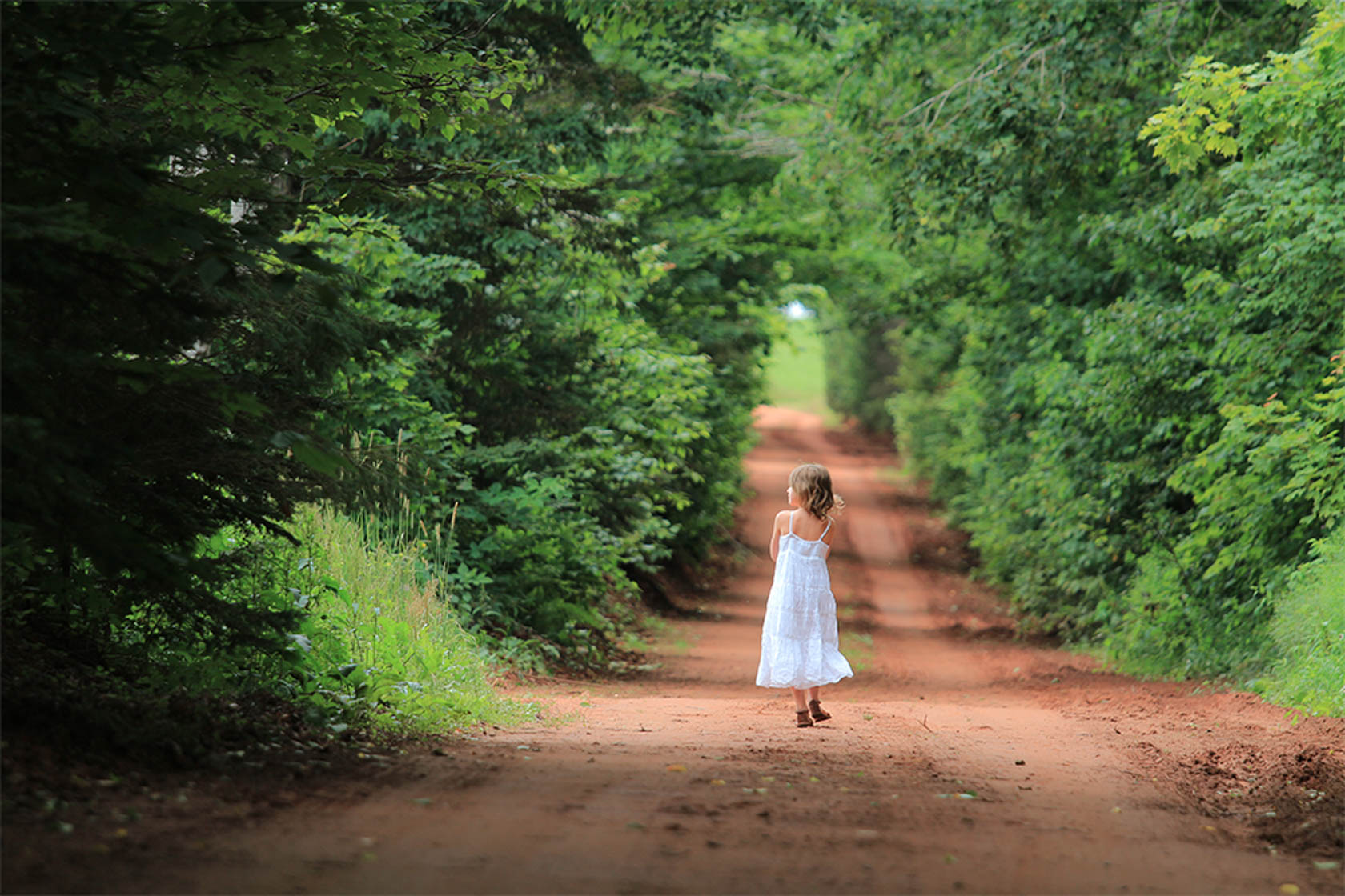 Young girl walking down a dirt road shot on Canon EOS M10 Compact System Camera