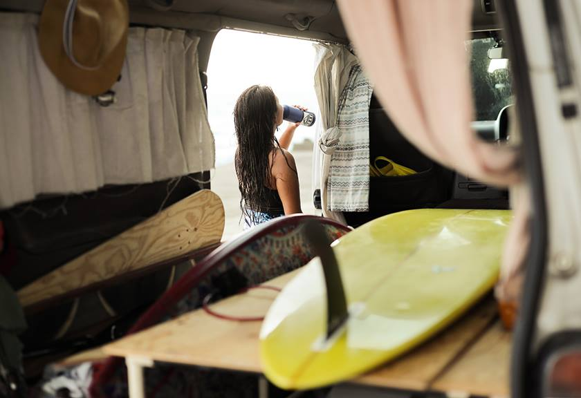 Image of a surfboard inside a van with a surfer in the background. Photo taken with the EOS R