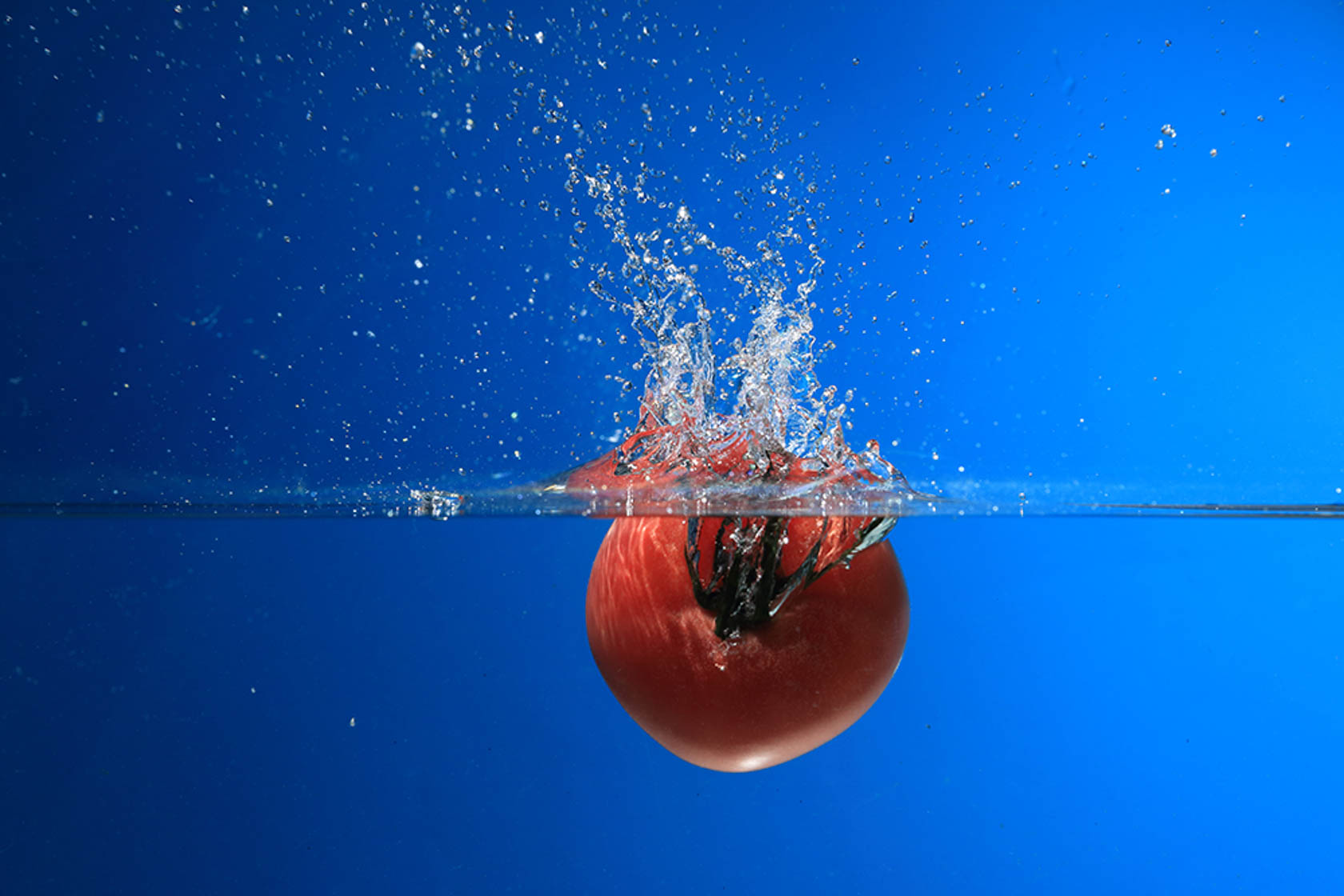 Tomato dropping into water taken using Canon Speedlite 430EX III-RT flash