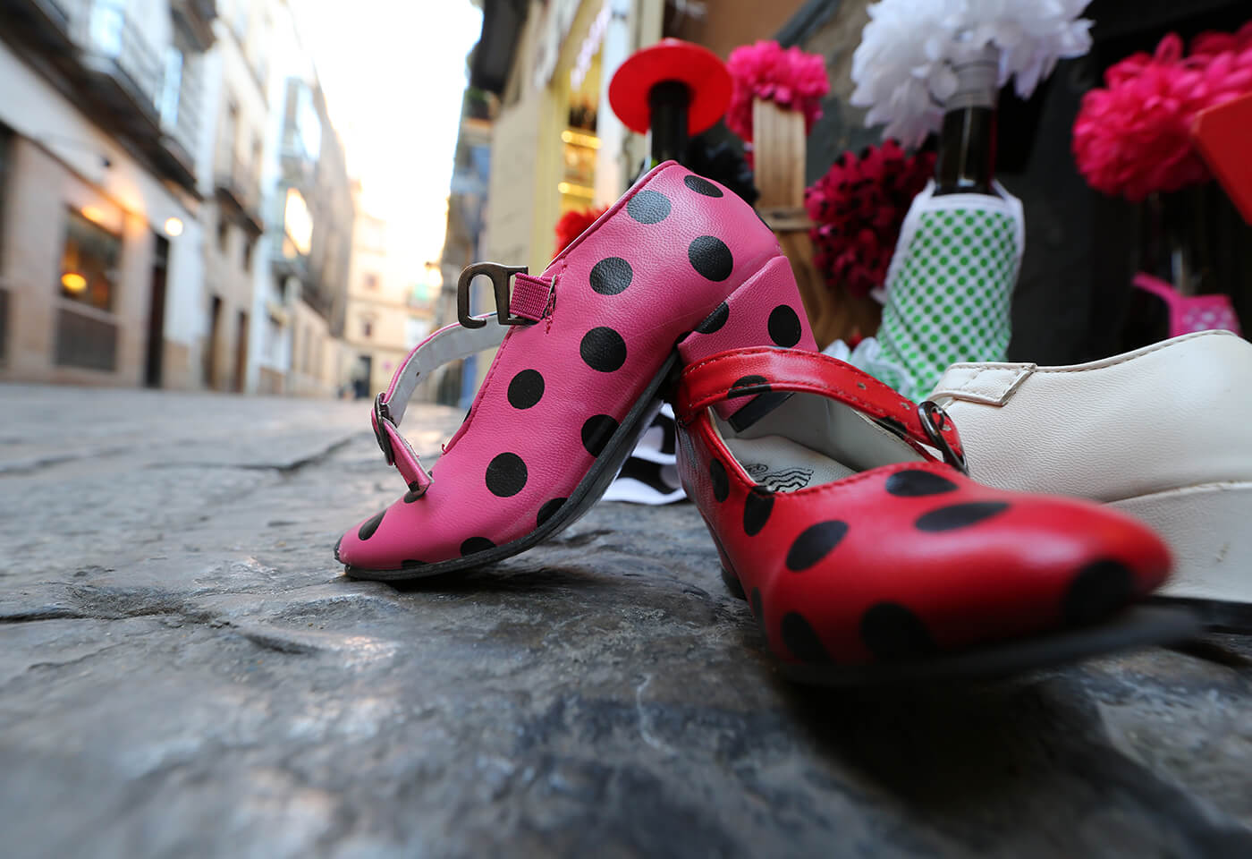 Pink and black polka dot shoes on street