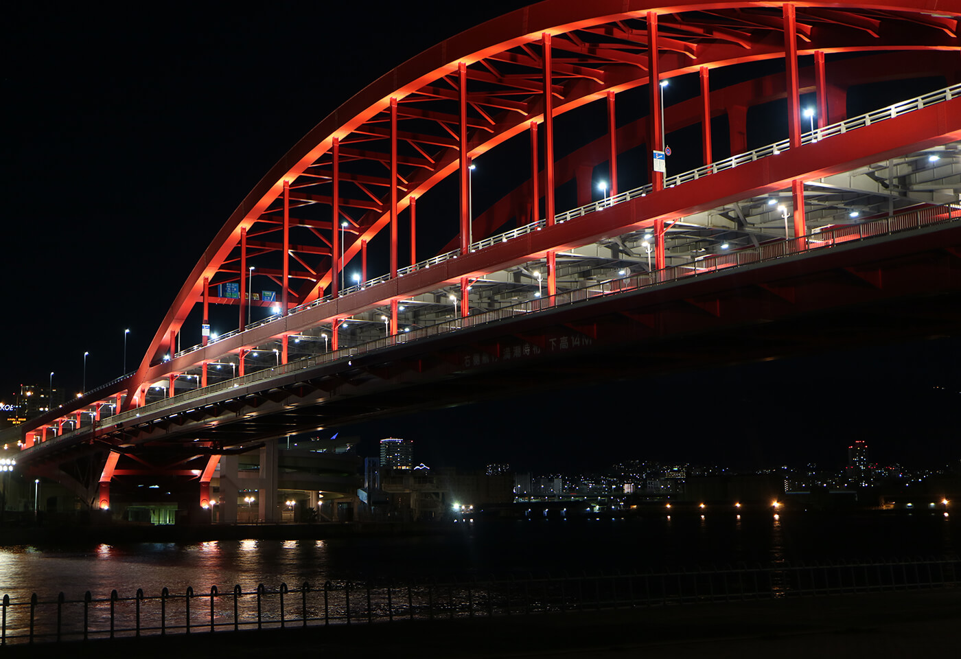Bridge covered in red lighting at night