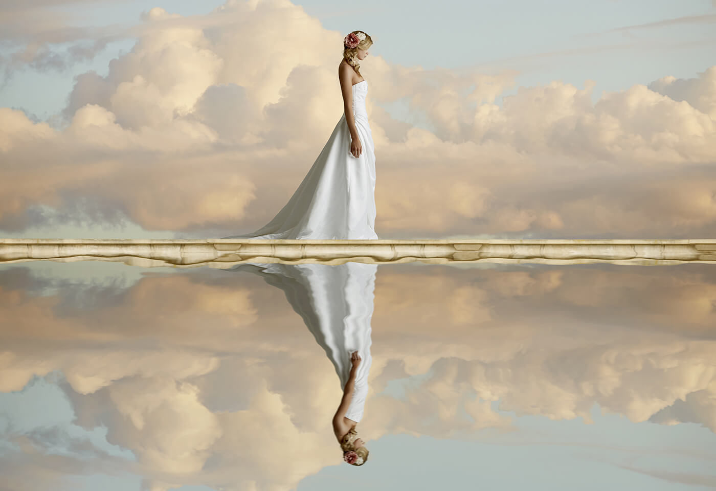 woman in wedding dress reflected in water