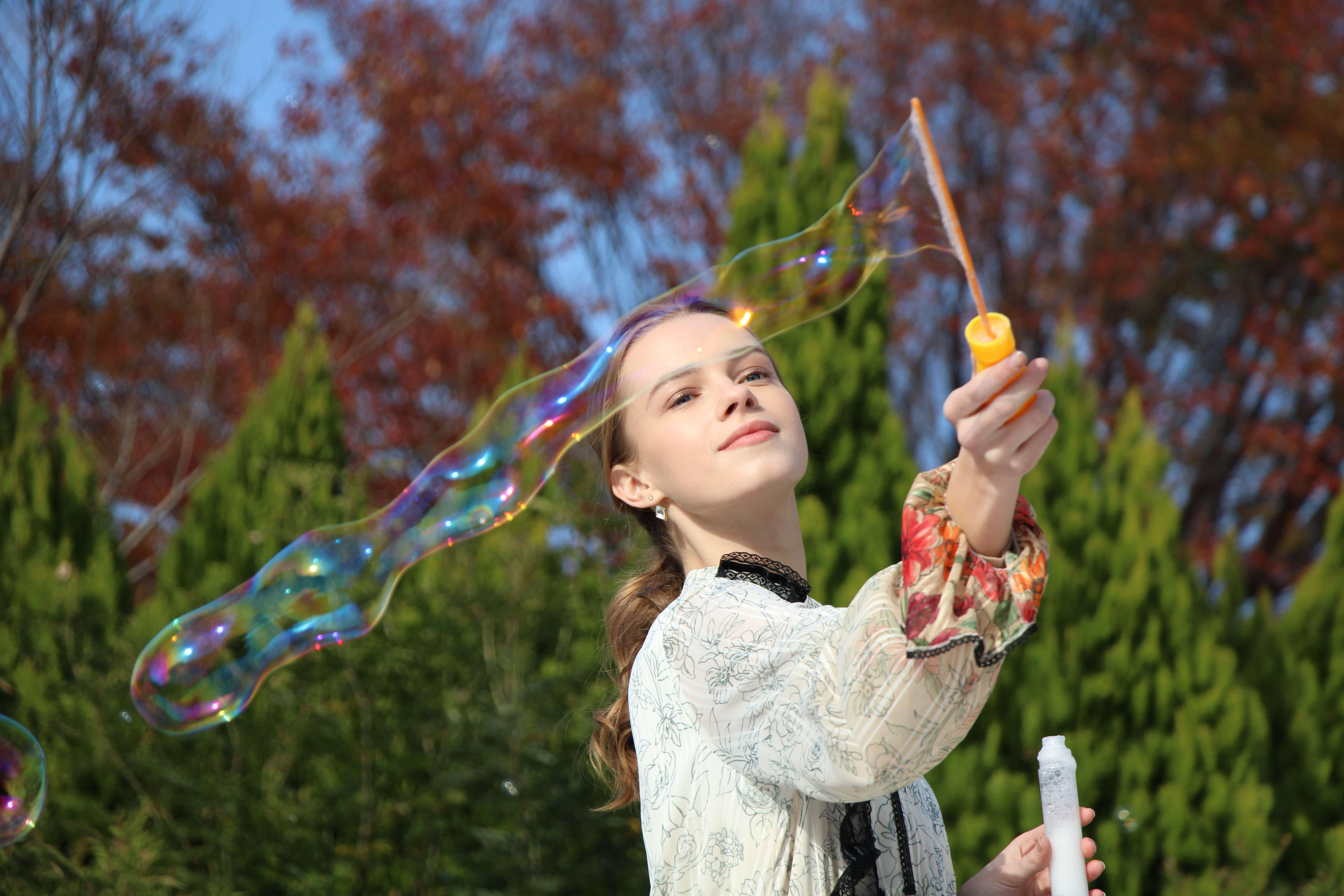 Portrait image of girl clowing bubbles taken with EOS 1500D