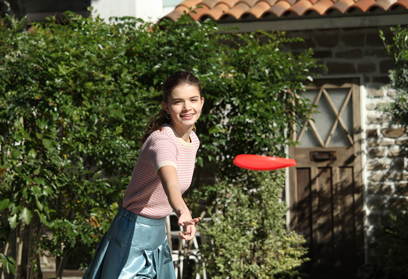 Portrait image of girl playing frisbee taken with EOS 3000D