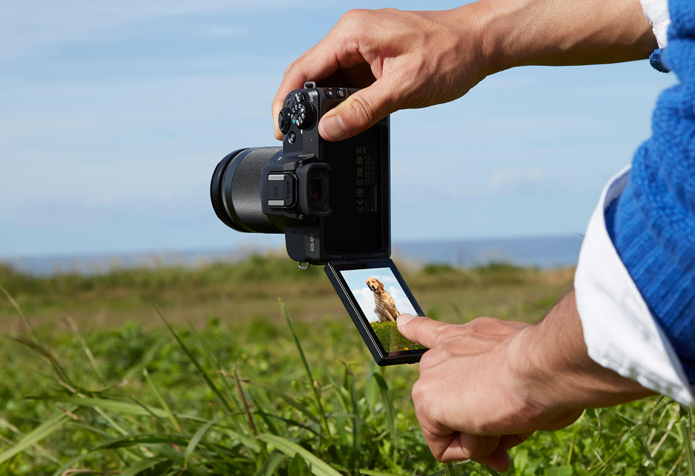 Image of man taking a photo with an EOS M50