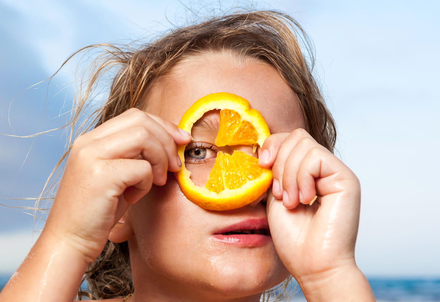 Portrait image of kid holding orange up to eye