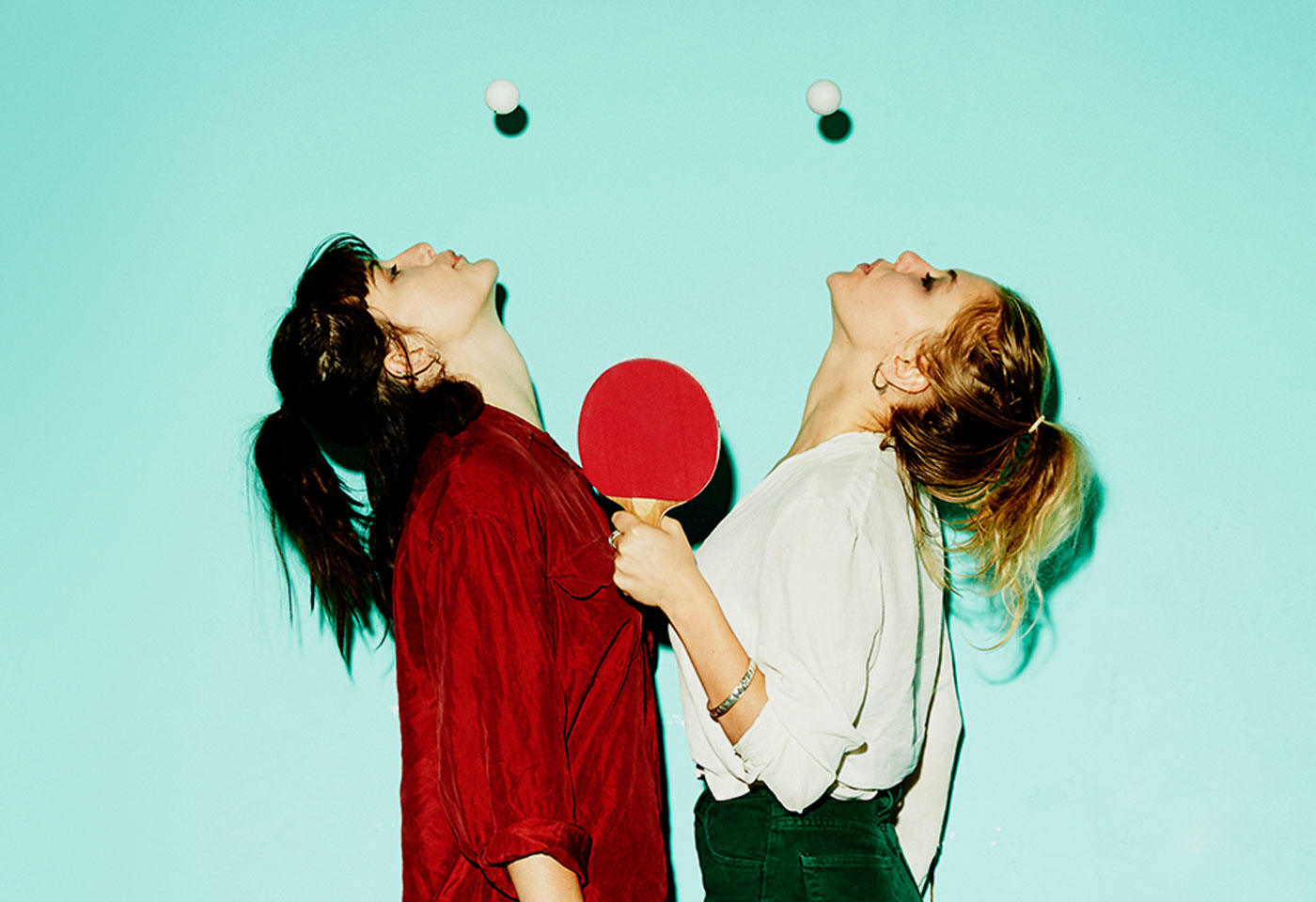 two girls with ping pong balls in the air