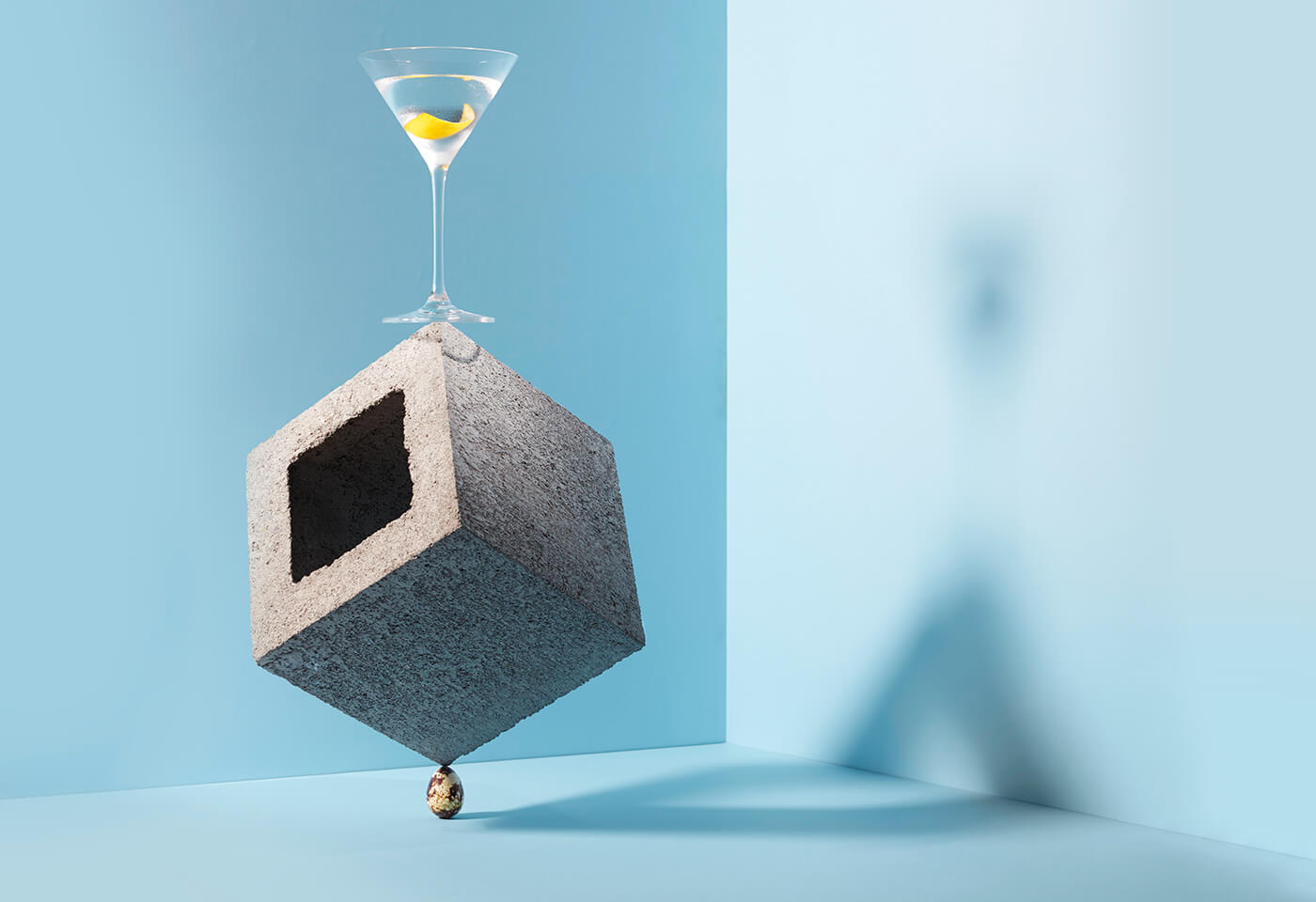 Still life image of cocktail glass balanced on concrete block by Danny Eastwood