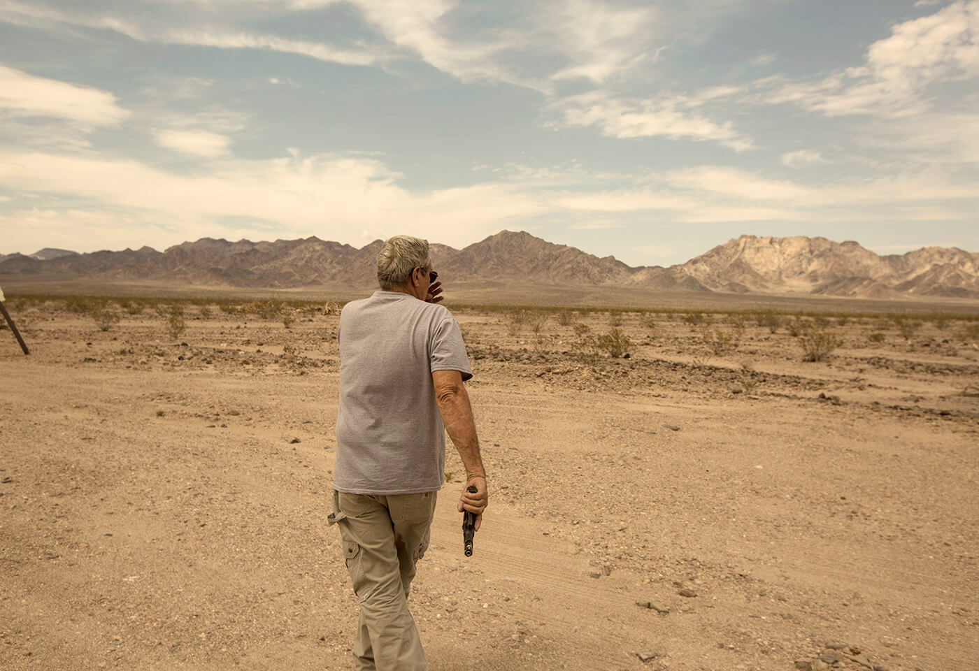 Image of man in desert with a handgun by Juliet Taylor