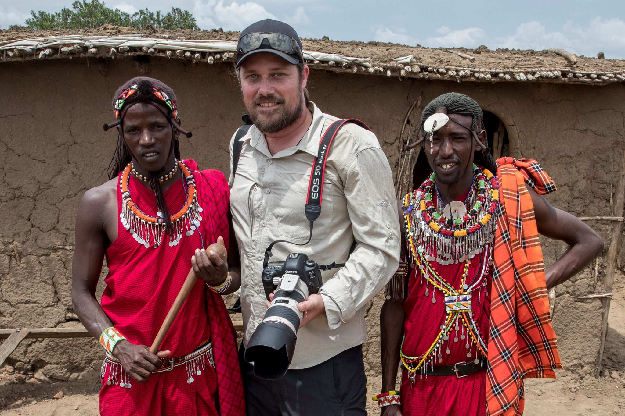 Portrait image of Jay Collier with two women in Africa