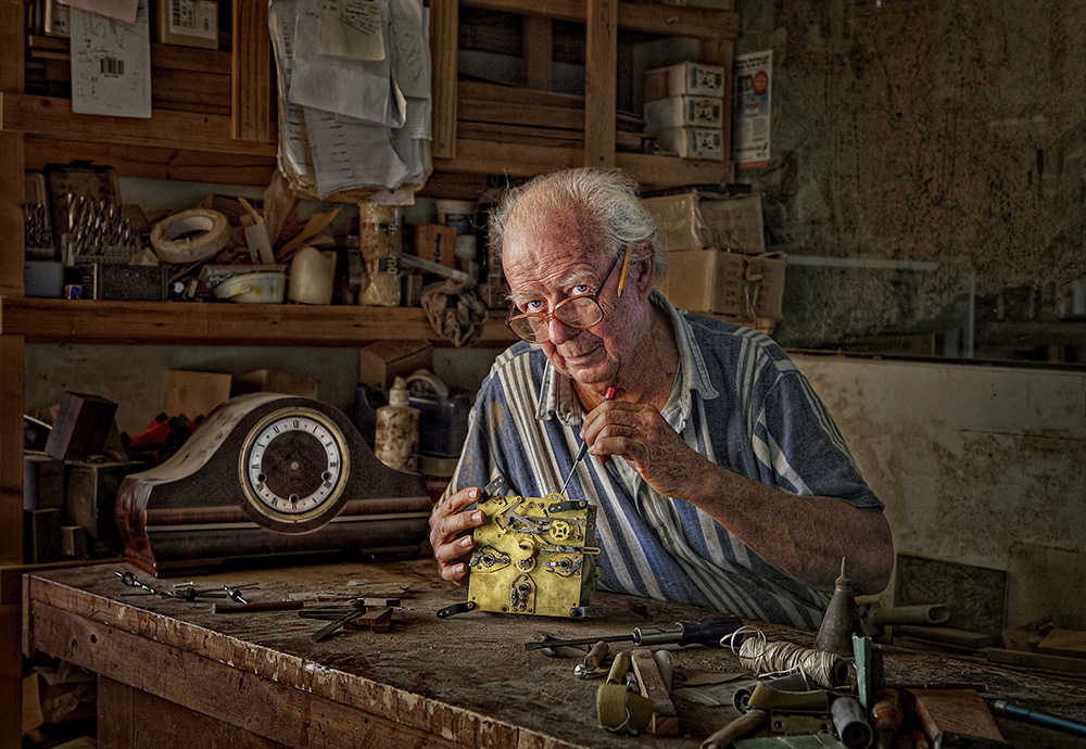 image of an elderly man fixing a clock