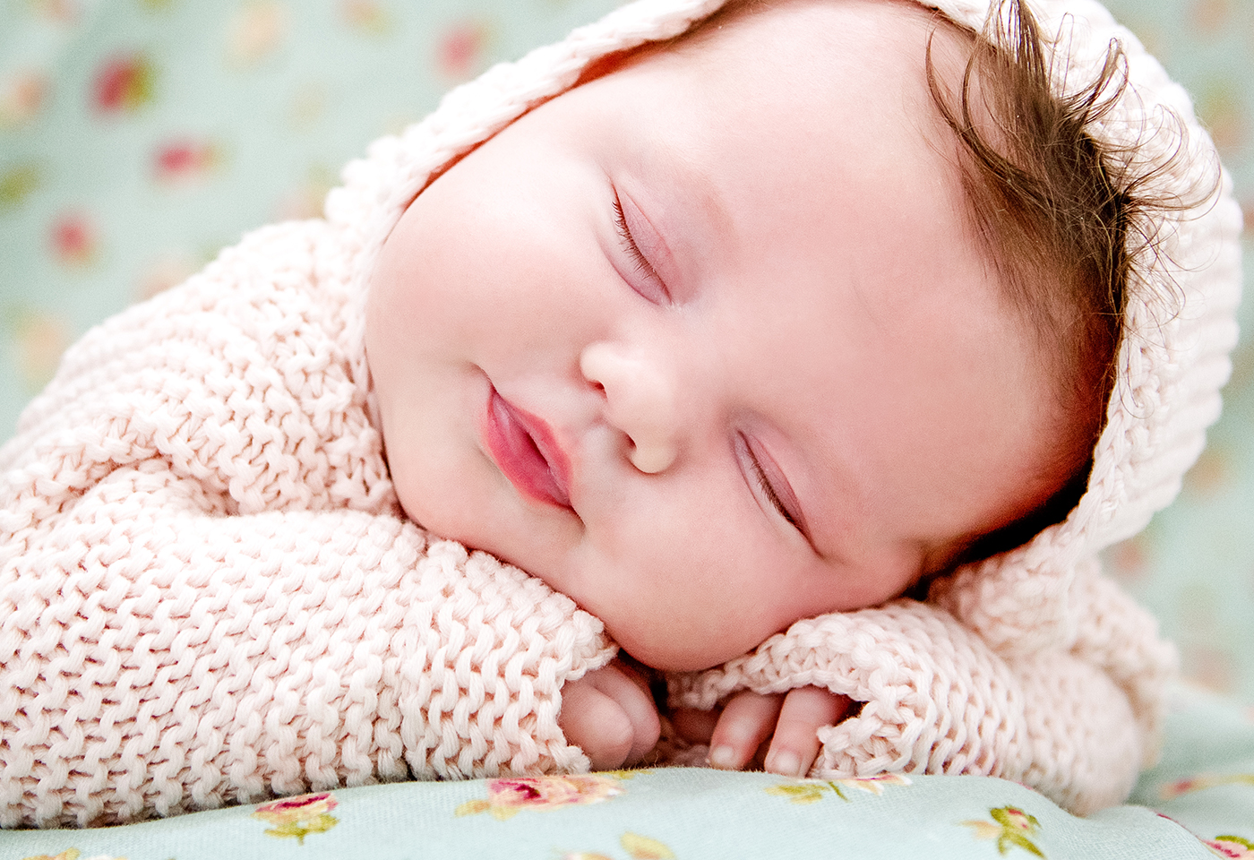 Portrait image of baby sleeping in pink suit by Willow Belle