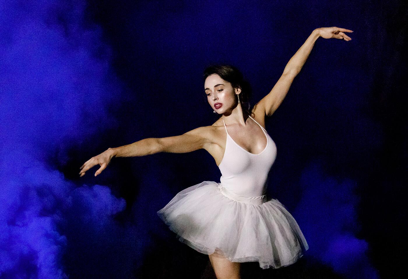 Ballerina dancing with blue coloured smoke