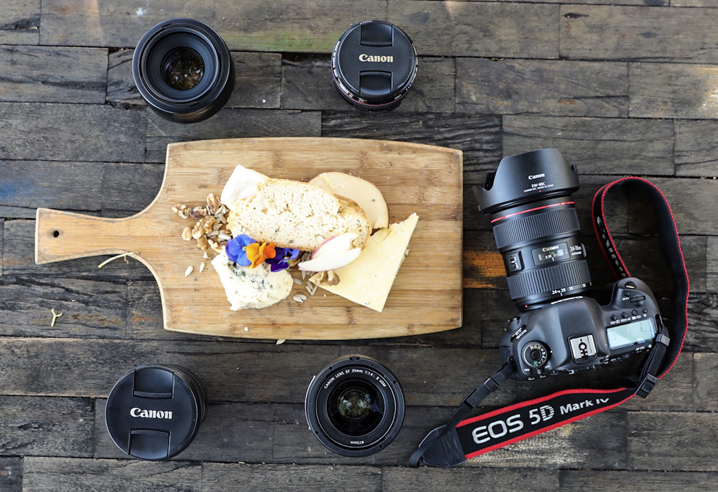 Camera and lenses around cheese board
