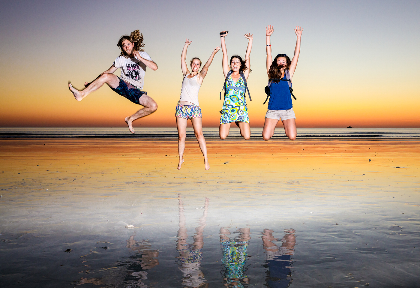 Image of four people jumping on a beach at sunset
