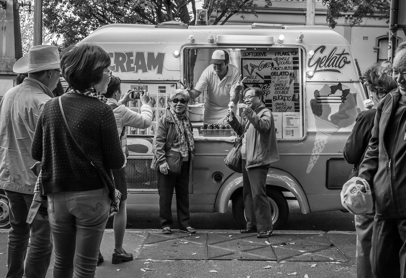 Tourists pose for photo next to icecream truck