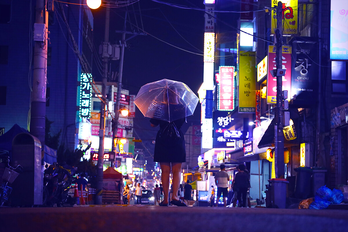 Angela standing under umbrella on a street of Korea at night