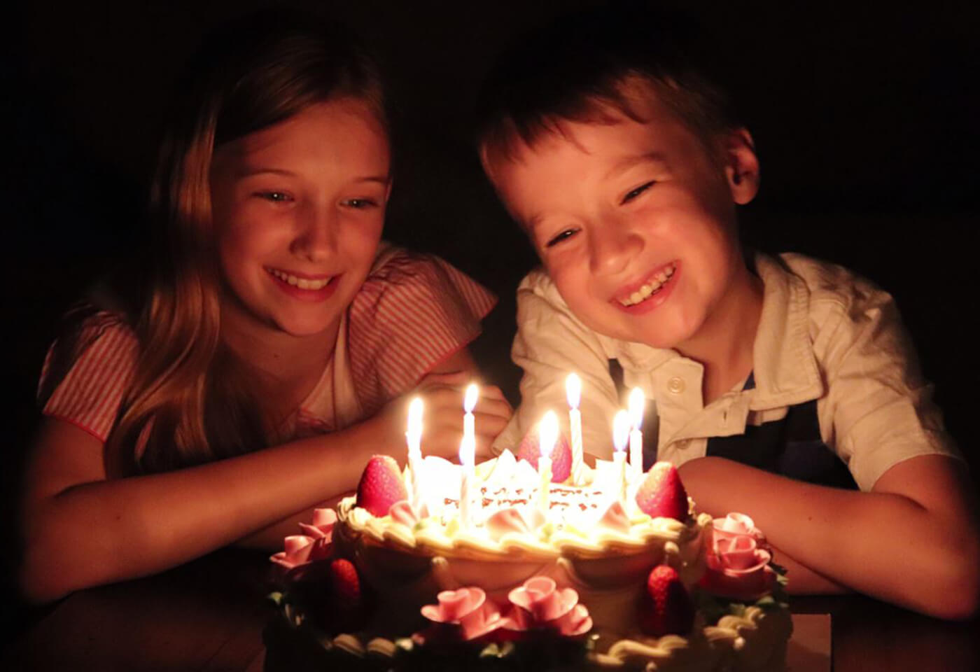 Low light image of two kids with candles on birthday cake