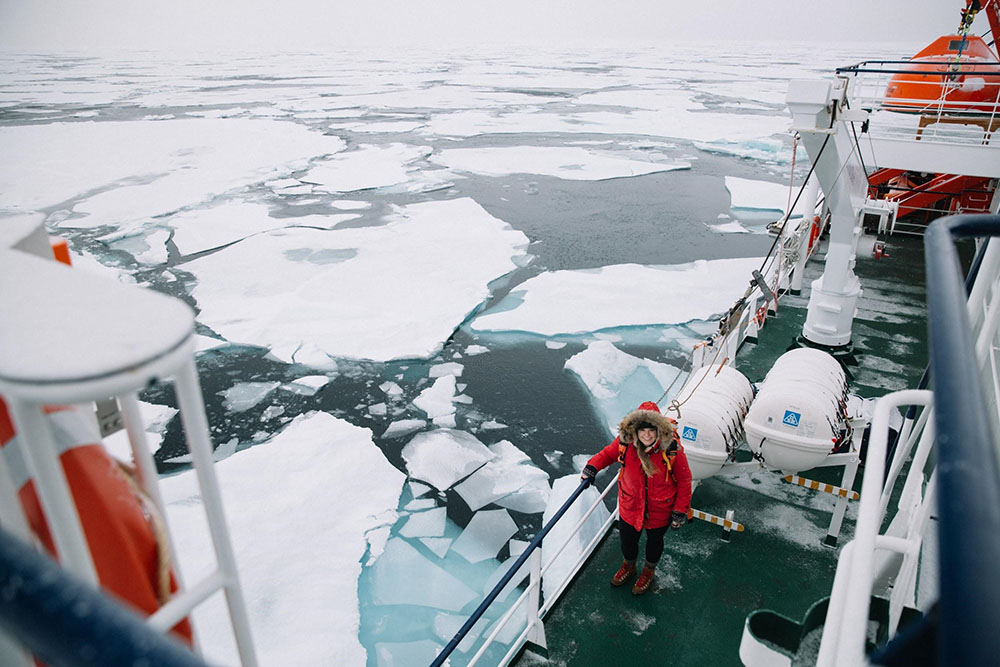 Landscape image of Liz Carlson on a boat in the artic