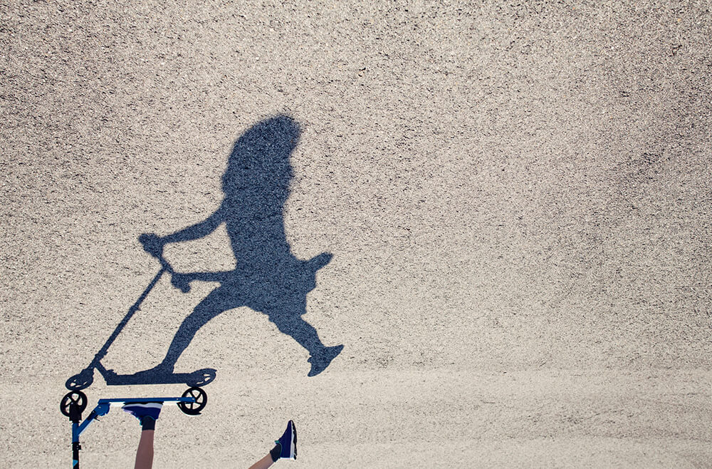 Shadow on pavement of child on scooter