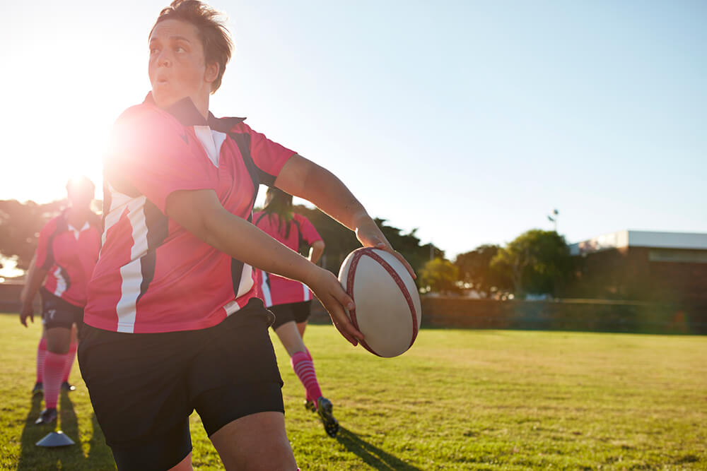 Female team playing rugby on field