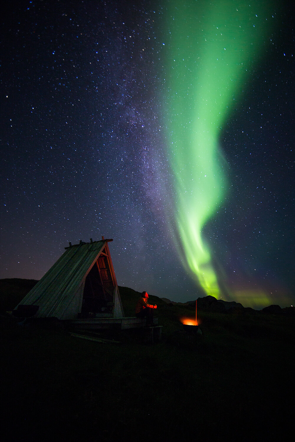 A person in front of a bonfire under the northern lights. Image by Neil Bloem