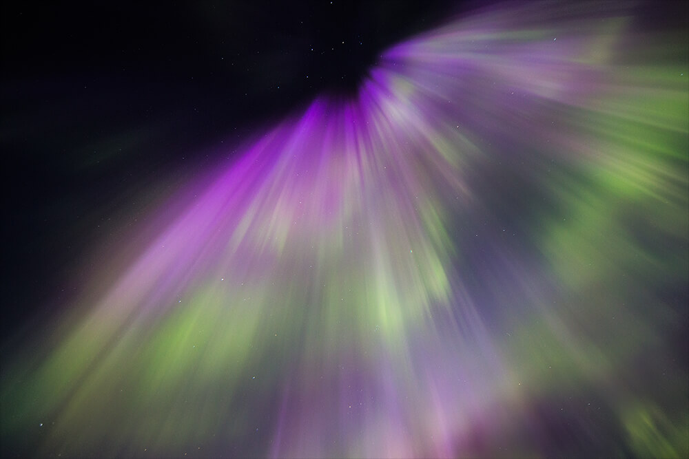photography of the Northern Lights with purple tones. Shot by Neil Bloem