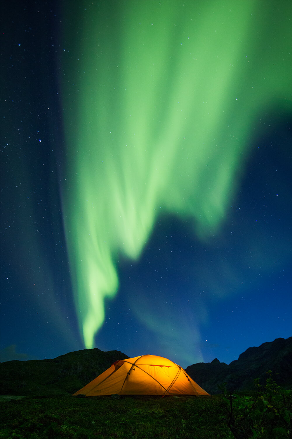 photo of a camping tent under the Northern Lights. Image by Neil Bloem