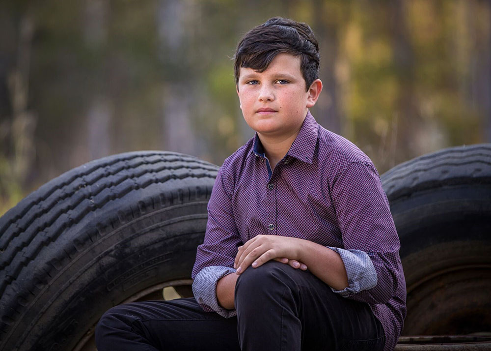 portrait image of boy sitting on tires